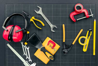 Top view shot of various reparement tools and ear muffs on graph paper stock vector