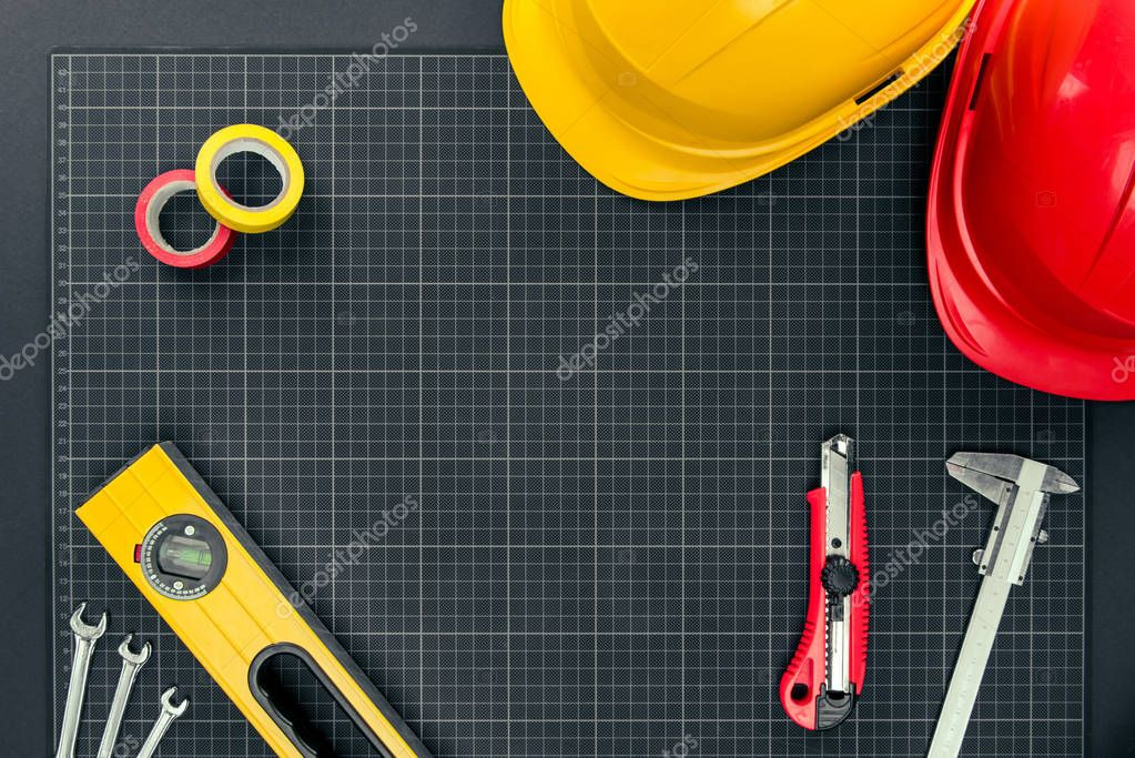 tools and hardhats on graph paper