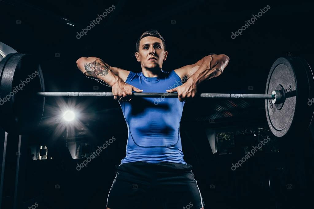athletic sportsman lifting barbell