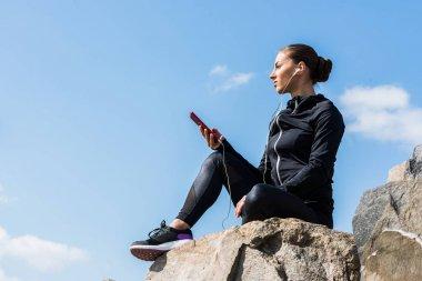 woman listening music on rocks