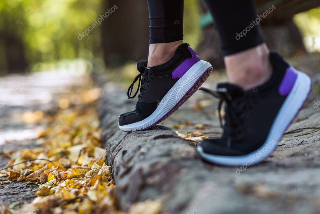 woman in sneakers at autumn park