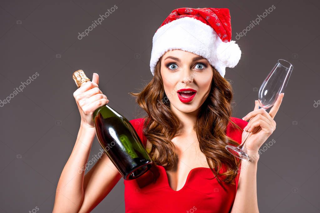 shocked girl in santa hat with champagne