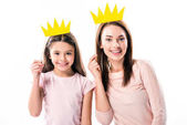 Mother and daughter with paper crowns on stick
