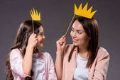 Daughter and mother holding paper crowns