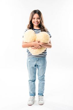child holding heart shaped pillow