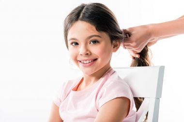 mother tying daughters hair in ponytail