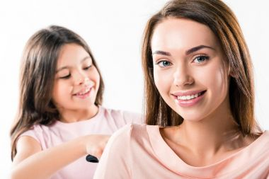 Daughter combing mothers hair