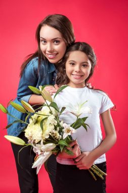 Daughter and mother posing with bouquet of flowers isolated on red stock vector