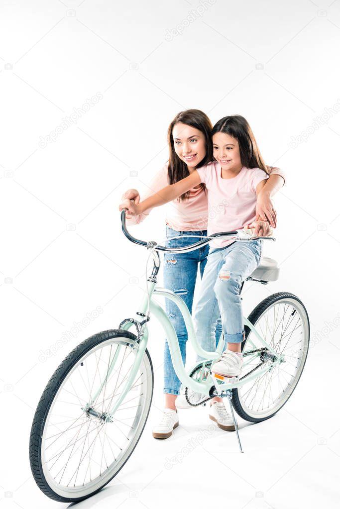 Mother teaching daughter riding bicycle