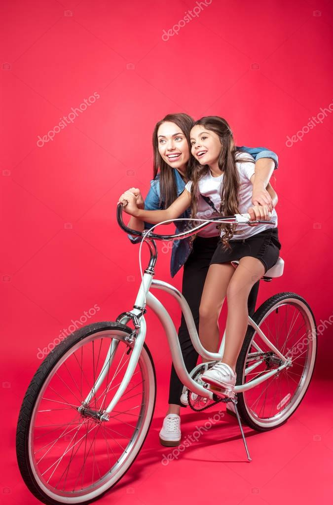 Mother teaching daughter riding bike