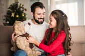 Photo father showing happy daughter teddy bear