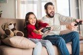 aufgeregter Vater und Tochter beim Videospiel zu Hause
