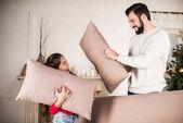 otec a dcera bije s polštáři doma