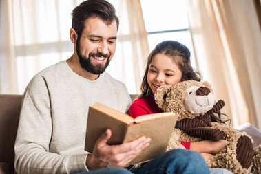 smiling father reading book to daughter