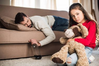 sad daughter sitting with teddy bear while drunk father sleeping on sofa