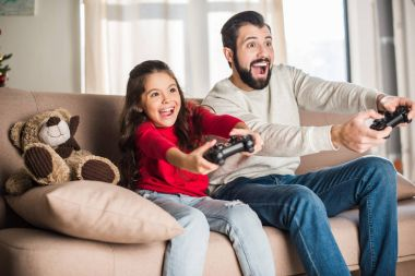 excited father and daughter playing video game at home