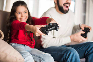 cropped image of father and daughter playing video game with game pads
