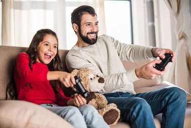 smiling father and daughter playing video game at home