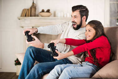 happy father and daughter playing video game at home