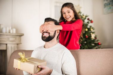 smiling daughter covering father eyes from back