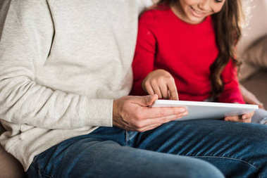 cropped image of daughter showing something on tablet to father