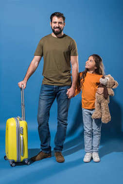 father and daughter standing with yellow travel bag and teddy bear on blue
