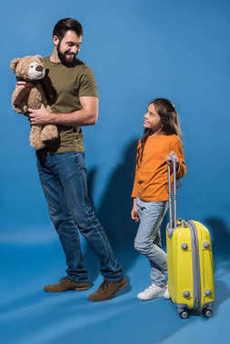 father with teddy bear and daughter with bag on wheels looking at each other on blue