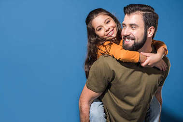 father giving piggyback to smiling daughter on blue