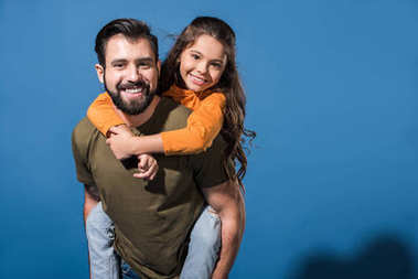 smiling father giving piggyback to daughter on blue