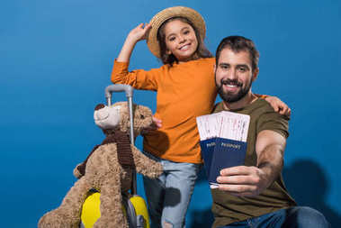 father and daughter with passports and tickets going on vacation on blue