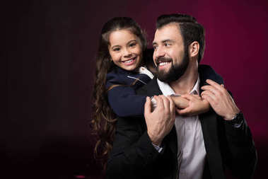 smiling daughter hugging father from back on burgundy