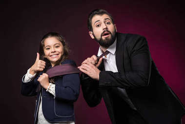 daughter showing thumb up and pulling father tie on burgundy