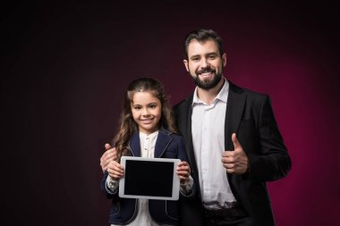 daughter holding tablet and father showing thumb up on burgundy