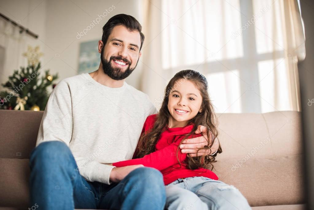 happy father and daughter hugging and looking at camera