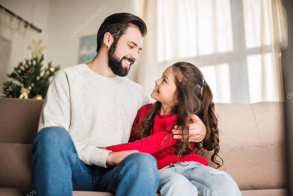happy father and daughter hugging and looking at each other