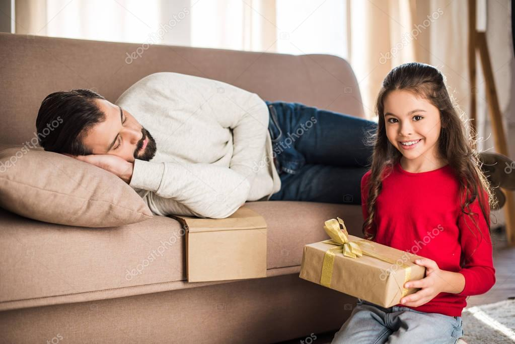 daughter holding gift box while father sleeping on sofa