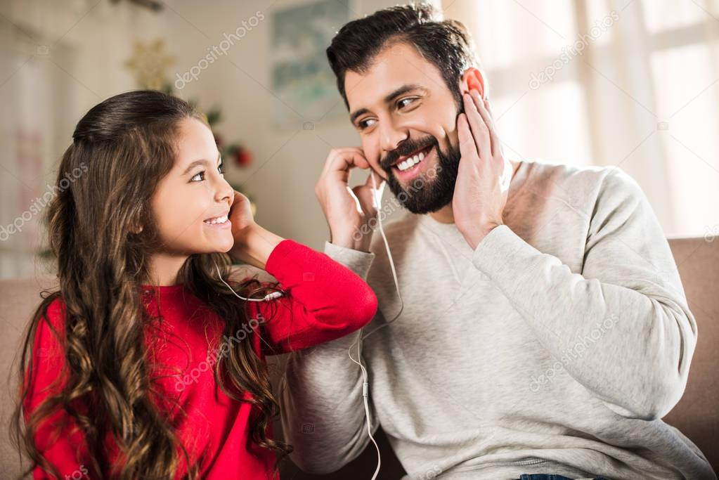 happy father and daughter listening to music with earphones