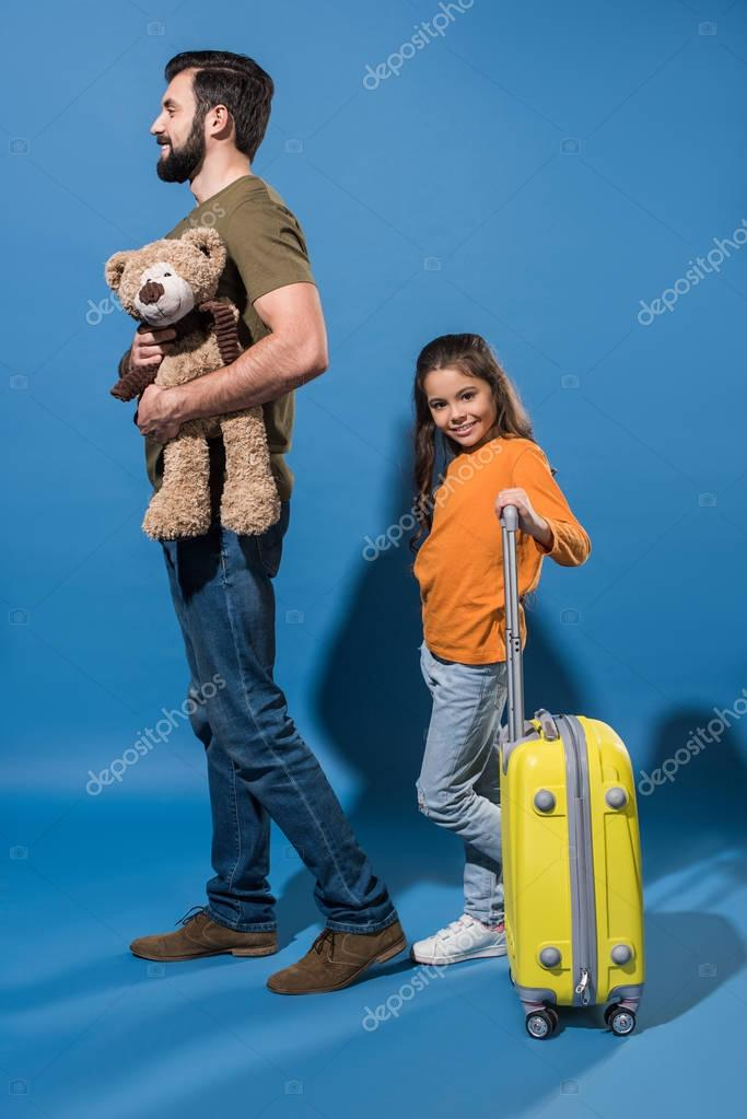 father with teddy bear and daughter with bag on wheels on blue