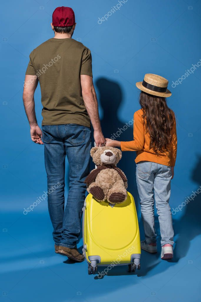 rear view of daughter and father going with travel bag on blue