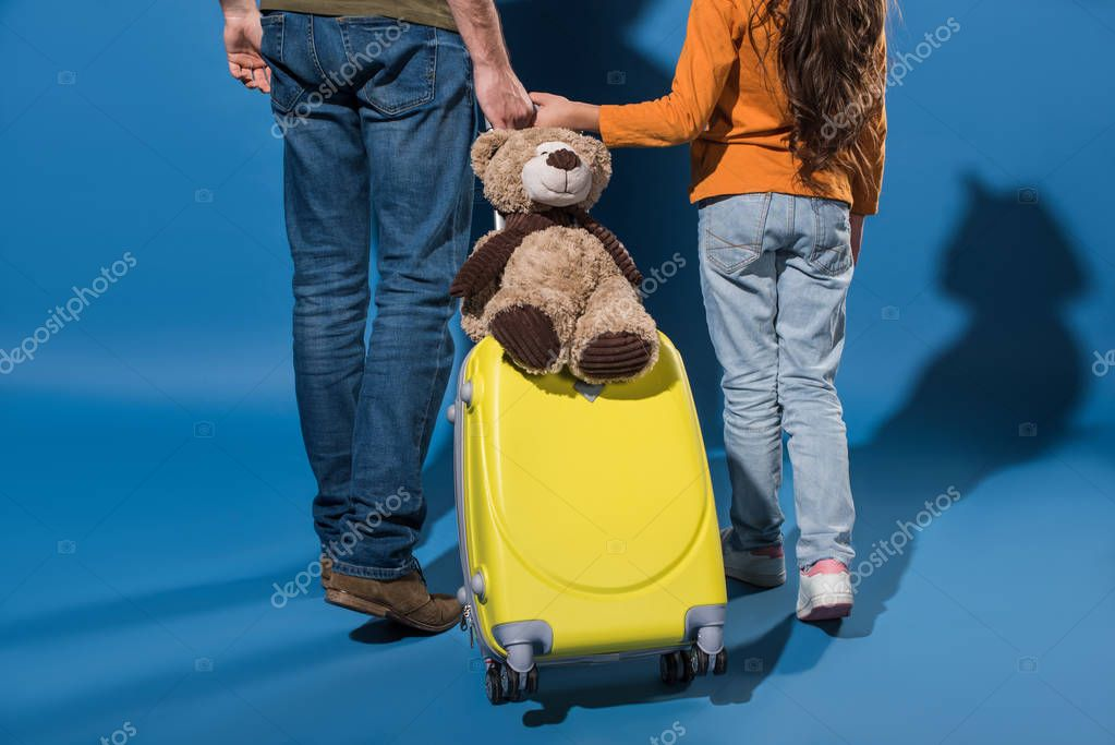 cropped image of father and daughter going with travel bag on blue