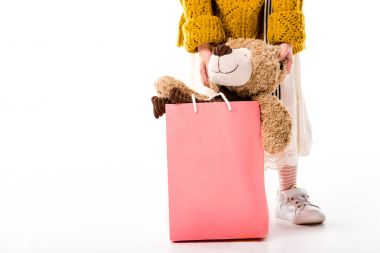 cropped image of kid standing with teddy bear in shopping bag on white