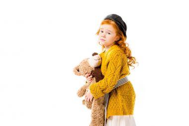 upset red hair kid hugging teddy bear isolated on white