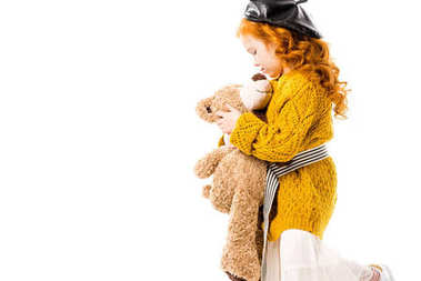 red hair child hugging teddy bear isolated on white