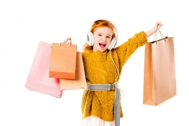 redhead child singing and holding shopping bags isolated on white