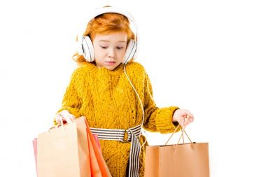 surprised red hair child looking at shopping bags in hands isolated on white