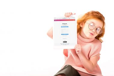 red hair kid sitting and showing loaded instagram page on tablet isolated on white