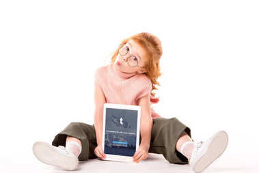 red hair child sitting and holding tablet with loaded tumblr page on white