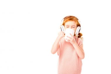 redhead kid drinking tea and listening music in headphones isolated on white