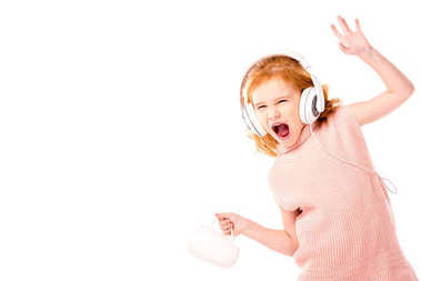 red hair kid in headphones screaming and dancing with cup isolated on white