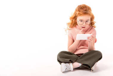 redhead kid looking at smartphone with surprise on white